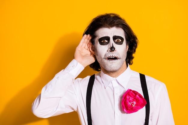 Foto van griezelige zombie met haren man hand oor probeer afluisteren verre kerkhof mensen delen nepnieuws dragen wit overhemd roos suiker schedel dood kostuum bretels geïsoleerde gele kleur achtergrond