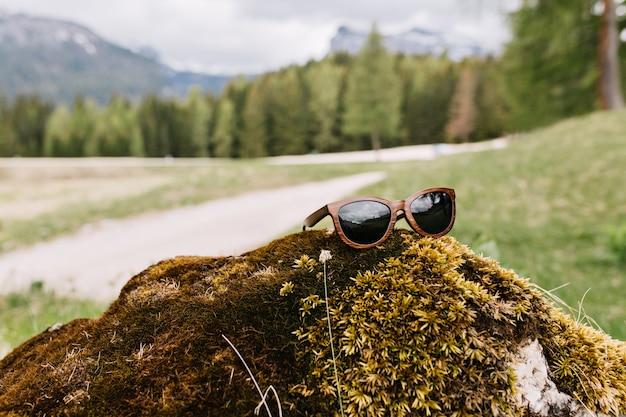 Foto van groen landschap met bergen en bos in de verte met trendy zonnebril op voorgrond