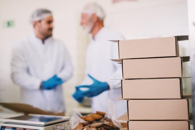 Foto van groep dozen in voedselfabriek. wazig beeld van twee man koekjes inpakken en praten op de achtergrond.