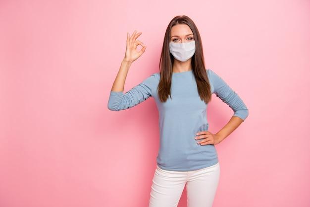 Foto van haar, mooi, gezond, aantrekkelijk meisje met een ok-teken met een veiligheidsgaasmasker, ziekte, ziekte, preventie, grieptherapie, geneeskunde, geïsoleerde, pastelroze kleurachtergrond