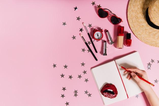 Foto van hand die aantekening maakt in notitieboekje met creatief verspreide cosmetica en zomeraccessoires voor dames