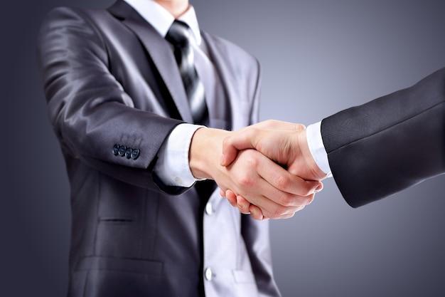 Foto van handdruk van zakenpartners na ondertekening van veelbelovend contract