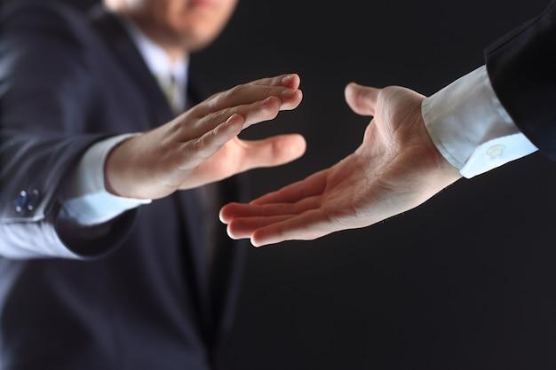 Foto van handen van zakenpartners vóór handdruk op zwarte achtergrond