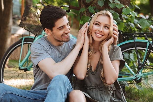 Foto van happy mooie jonge paar samen zitten en luisteren muziek buiten