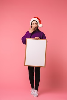 Foto van het geschokte gelukkige jonge emotionele vrouw stellen geïsoleerd over roze holdings copyspace leeg.