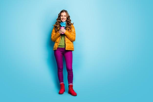 Foto van het hele lichaam van mooie dame die heet papier drank mok geniet van warm weer draag casual gele overjas sjaal violet broek rode schoenen trui geïsoleerde blauwe kleur muur