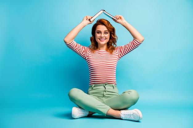 Foto van het hele lichaam van positieve vrolijke vrouw zitten benen gekruist vasthouden papieren boek boven het hoofd zorgeloos voelen op cursussen dragen witte groene broek broek geïsoleerd over blauwe kleur