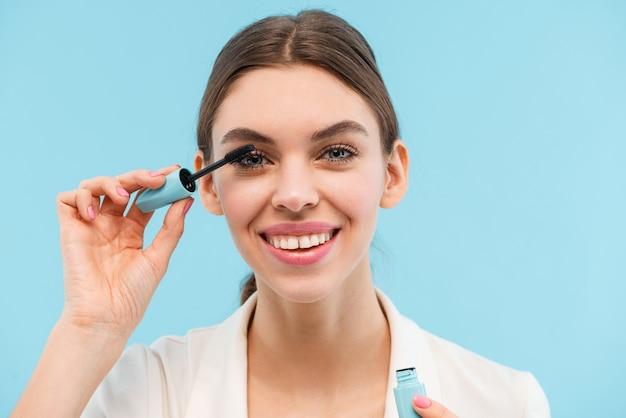 Foto van het mooie jonge vrouw stellen geïsoleerde de mascara die van de holdingszweep make-up doen.