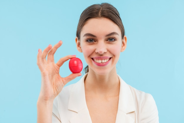 Foto van het mooie jonge vrouw stellen geïsoleerde holdingslippenbalsem.