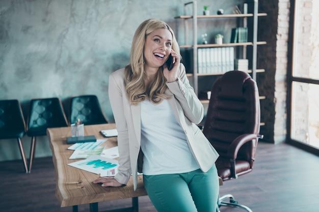 Foto van het positieve de telefoon van de bedrijfsdameegreep spreken