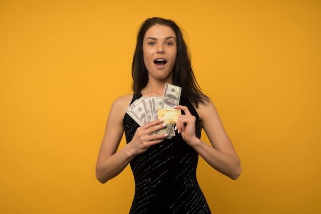 Foto van het tevreden gelukkige jonge vrouw stellen geïsoleerd over gele muur als achtergrond met geld en krediet- of schuldkaart.