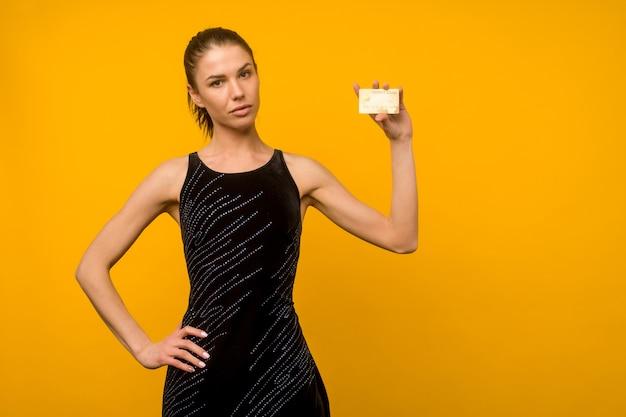 Foto van het tevreden jonge vrouw stellen geïsoleerd over gele muur met debet- of creditcard als achtergrond.