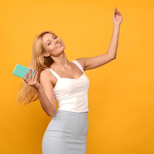 Foto van het tevreden jonge vrouw stellen geïsoleerd over gele muurachtergrond die mobiele telefoon met behulp van. - afbeelding