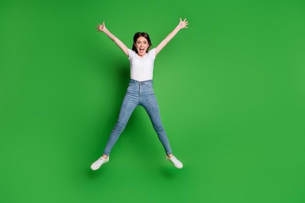 Foto van het volledige lichaam van een energieke meisjessprong die de handen opsteekt, geïsoleerd over een groene felle kleurachtergrond