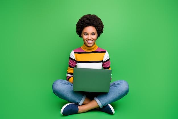 Foto van het volledige lichaam van positieve afro-amerikaanse meisje zitten benen gekruist gevouwen werk op computer smm werknemer concept dragen stijlvolle denim jeans outfit Premium Foto