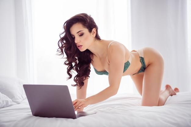 Foto van hete geile dame thuis werken op afstand online laptop chat uitkleden vormen tonen schrijven antwoord cliënt klaar toon meer voor geld staan knieën kat pose draag bikini lakens slaapkamer binnenshuis