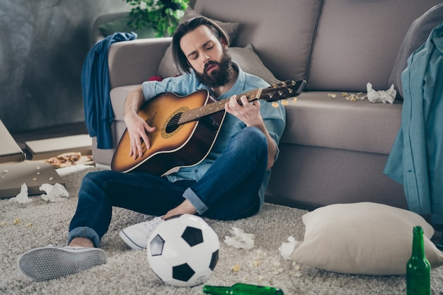 Foto van hipster man met lange baard zittend tapijt in de buurt van bank houden gitaar niet erg chaos na vrijgezellenfeest rommelig vuile platte zingende liedjes onzorgvuldig persoon binnenshuis
