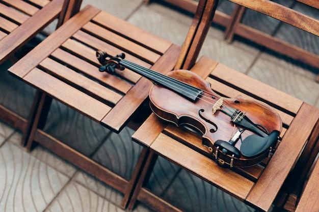 Foto van houten viool op stoelen.