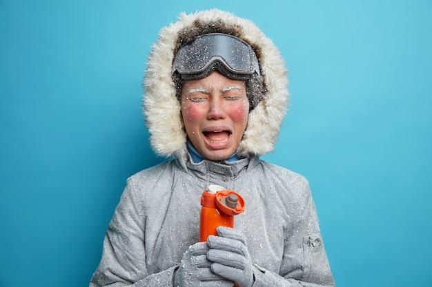 Foto van huilende boos vrouw toerist besteedt wintervakantie voelt actief erg koud na het skiën in sneeuwstorm of sneeuwstorm drinkt hete thee of koffie uit thermos draagt grijze jas met bont capuchon