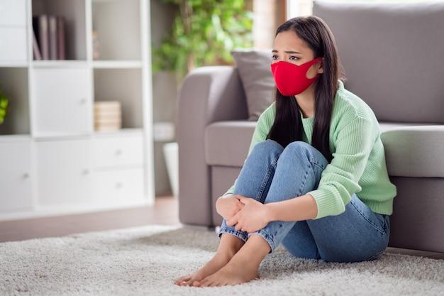 Foto van huiselijk verdrietig corona-virus zieke patiënt aziatische dame zit op de vloer tapijt bank houd benen knieën vast die lijden aan infectie ziekte zelfisolatie sociale afstand blijf thuis quarantaine binnenshuis