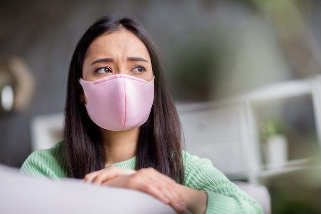 Foto van huiselijk verdrietig corona-virus zieke patiënt aziatische dame zittend op de bank kijk dromerig raam ontbreekt naar buiten gaan zelfisolatie houden sociale afstand blijf thuis quarantaine binnenshuis