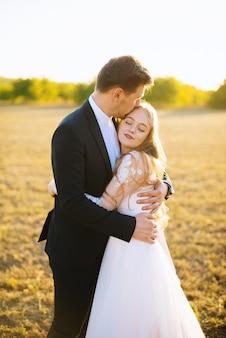 Foto van huwelijkspaar, bruidegom die bruid koesteren en op het voorhoofd kussen, die zich in ingediend op zonsondergang bevinden