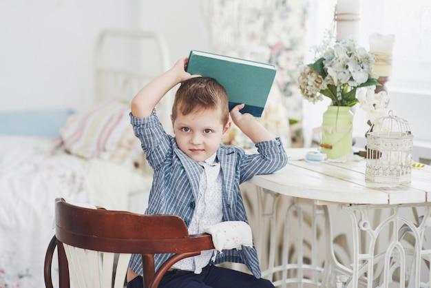 Foto van ijverige schooljongen met boek op zijn hoofd wil niet studeren en naar school gaan. de schooljongen is moe van het maken van huiswerk