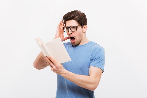 Foto van intellectuele kerel die oogglazen draagt die boek in verontwaardiging lezen, die over witte muur wordt geïsoleerd