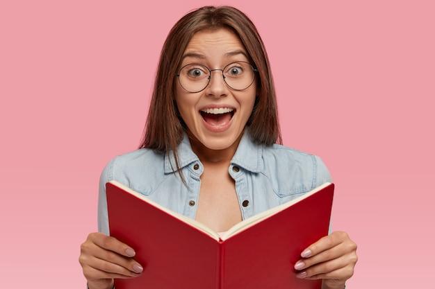 Foto van intelligente europese vrouwelijke wonk houdt geopend boek vast, voelt zich blij om een romantisch verhaal tot einde te lezen, voelt zich opgewonden met onverwachte gebeurtenis, draagt een spijkerjasje en ronde bril, staat binnen