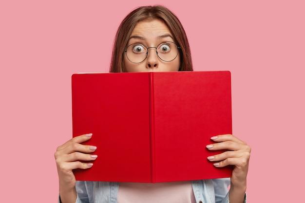 Foto van intelligente vrouwelijke student bedekt gezicht met rood boek, staart met afgeluisterde ogen, voelt geschokt om plotseling nieuws te horen, propt voor examen op de universiteit, geïsoleerd over roze muur