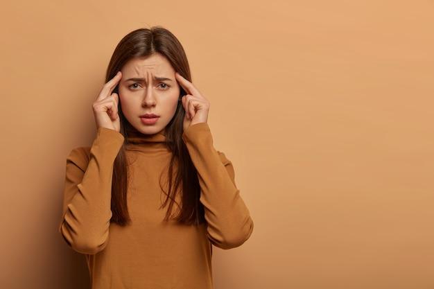 Foto van intense blanke vrouw raakt tempels met wijsvingers, grijnst gezicht, lijdt aan hoofdpijn of migraine, voelt zich ziek en lastig gevallen