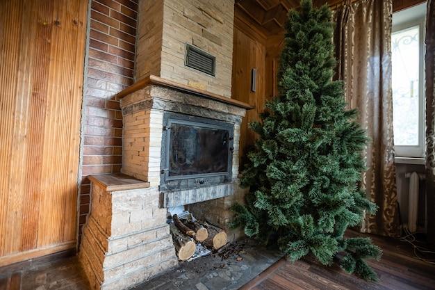 Foto van interieur van kamer met een houten muur, kerstboom, open haard. kerst sfeer. thuiscomfort