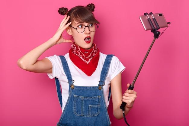 Foto van jong donkerharig tienermeisje die selfie foto voor sociaal netwerk op roze nemen