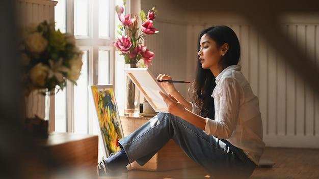 Foto van jong kunstenaarsmeisje die een verfborstel houden en olieverf trekken op canvas