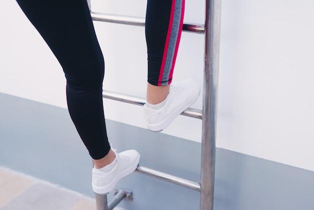 Foto van jong meisje dat stap voor stap op ladder klimt