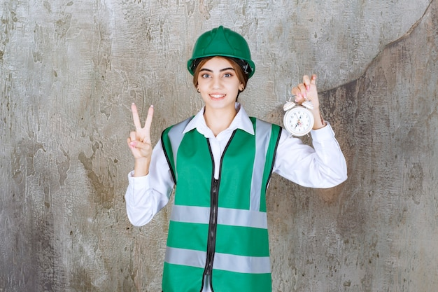 Foto van jong meisje in groen vest en veiligheidshelm met wekker die overwinningsteken toont