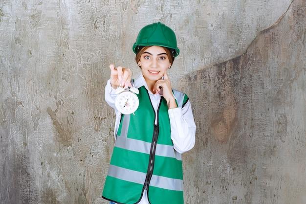 Foto van jong meisje in groen vest en veiligheidshelm met wekker