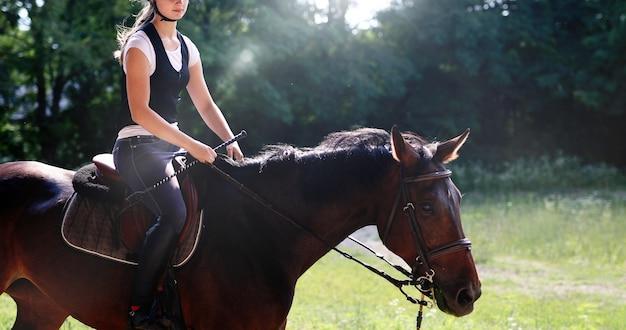 Foto van jong mooi meisje dat haar paard berijdt