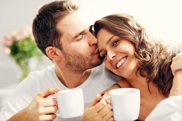 Foto van jong stel dat koffie drinkt in bed