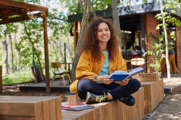 Foto van jonge aantrekkelijke donkere gekrulde student dame voorbereiding voor examen, plaatsing op een cafe terras, gekleed in gele jas, koffie drinken, breed glimlachen, geniet van studeren.