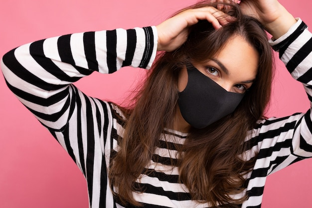 Foto van jonge aantrekkelijke vrouw die met de hand gemaakt katoenen stoffen gezichtsmasker draagt dat over kleurrijke achtergrondmuur wordt geïsoleerd. bescherming tegen covid-19.