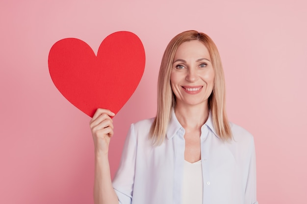 Foto van jonge aantrekkelijke vrouw met groot papieren hart groot hart valentijnsdag liefde romantiek geïsoleerd over roze achtergrond