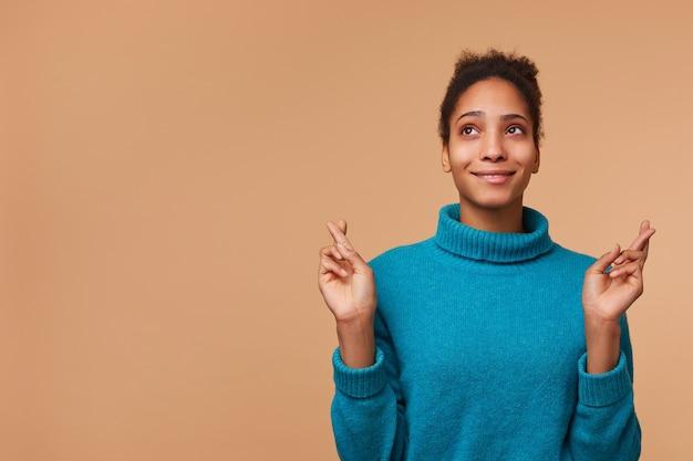 Foto van jonge afrikaanse amerikaanse dame die een blauwe sweater draagt, met donker krullend haar. met gekruiste vingers omhoog kijken en een wens doen. geïsoleerd op biege achtergrond met copyspace.