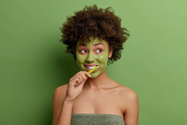 Foto van jonge afro-amerikaanse vrouw past groen gezichtsmasker borstels tanden gebruikt tandenborstel