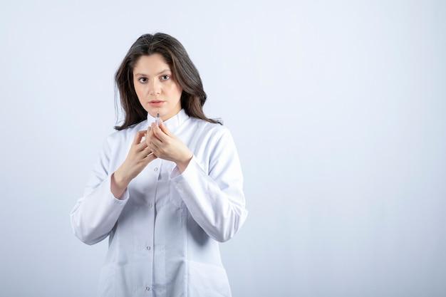 Foto van jonge arts met spuit die zich op grijs bevindt.