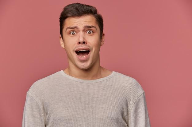 Foto van jonge bang man in lege lange mouw, staat op roze achtergrond met wijd open ogen en schreeuwen, ziet er gek en ongelukkig uit.