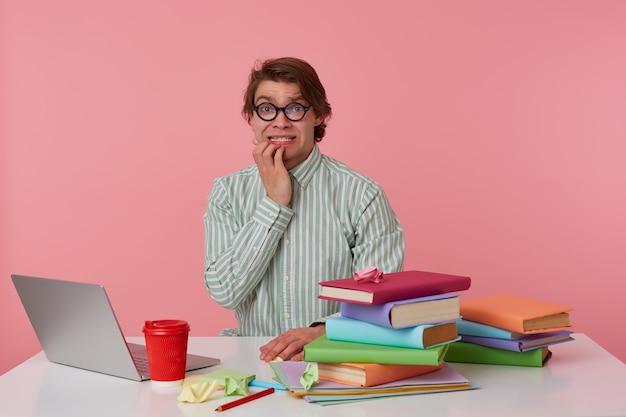 Foto van jonge bang man met bril, zit bij de tafel en werkt met laptop, knagende vingers, in de camera kijken met bange uitdrukking, geïsoleerd op roze achtergrond.