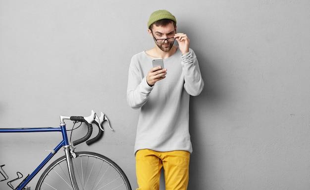 Foto van jonge bebaarde man met trendy hoed en kleding met een bril terwijl hij een vreemd sms-bericht van een onbekend nummer leest, naar het scherm tuurt, een verdachte of wantrouwende blik heeft