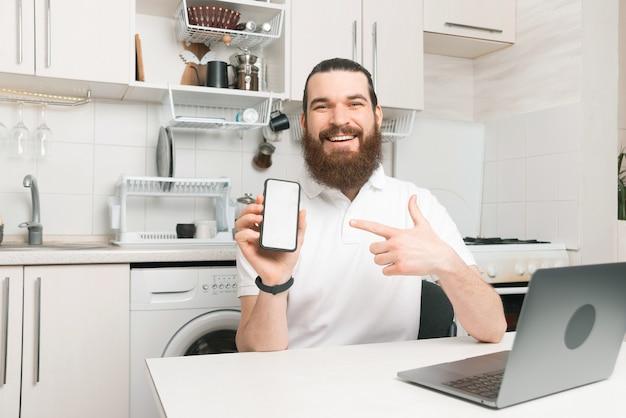 Foto van jonge bebaarde man werken vanuit huis zit aan bureau en wijzend op smartphone