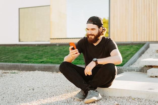 Foto van jonge bebaarde man zit voor zijn huis en met behulp van slimme telefoon en glimlachen